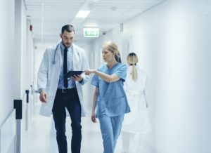Female Surgeon and Doctor Walk Through Hospital Hallway