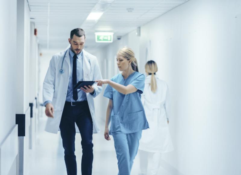 Female Surgeon and Doctor Walk Through Hospital Hallway
